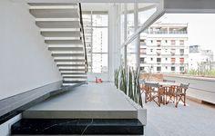 A reforma comandada pelos arquitetos Paula Zemel e Eduardo Chalabi começou com a substituição das escadas, que eram fechadas e pesadas. As novas são vazadas, com estrutura oculta. A da foto leva à varanda, que tem pé-direito duplo