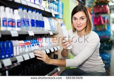 female shopper searching for deodorants from shelves in supermarket