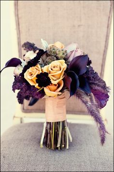 Orange and purple Bouquet with feathers peach and orange rose purple calla scabiosa pods
