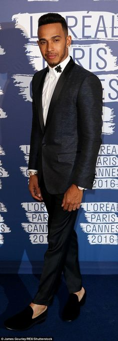 Style sensation: Lewis cut a dapper figure in a smart navy suit, wearing a white shirt underneath it which had embroidered flowers on the collar. Flashing a hint of ankle, he completed his look with a pair of velvet slippers
