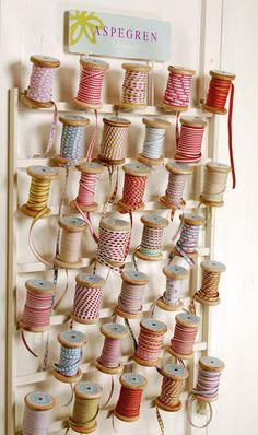 I love this idea! Use wood thread spools to store ribbon! CUTE!