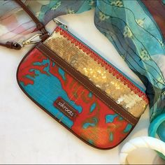 HP Coral/turquoise blingy sak roots wristlet So cute! Treated canvas in coral and turquoise. Feels kind of like heavy ripstop nylon. Front has fabulous gold sequin embelishment. Luggage tan trim. Zip top with wrist strap. One exterior pocket and one interior pocket. Fully lined interior. Key strap inside. Gently loved but still in excellent condition. [Matching tote found in closet of @amandaxoxo5 !] sakroots Bags Clutches & Wristlets