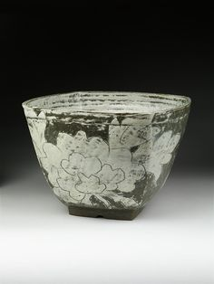 Formed on the potter's wheel, Huh Sang Wook's pot has been pounded to create straight walls out of the originally globular form. White clay has been applied to the surface. Flowers and leaves are carved into that white layer. The artist has scraped off the white clay to reveal the dark colour of the vessel, allowing the floral pattern to stand out. He has said that he wants to create a sense of space by emphasizing the contrast between pattern and background colour. He is interested also in…