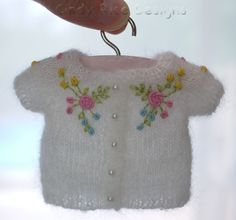 Patience's cardigan is hand knit our of mohair/silk lace yarn.  Bullion stitched roses/rosebuds are embroidered to coordinate with her dress.
