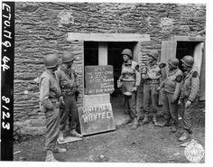 Groupe de soldats devant le premier café ouvert à Saint-Lô par le caporal E. L. Martin, 19 juillet 1944