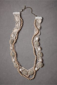 """Appliqued to ecru macramé lace, little shells made of beads both white and opaline are kept company by a string of champagne pearls and pearl edging. From Rada. Lobster claw closure. 31.5""""L, 1.4""""W. Glass pearls, glass beads, cotton lace macramé, brass. Handmade in Italy."""