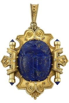 Egyptian Archaeological Revival Gold, Carved Lapis Scarab, Lapis and Diamond Pendant. The stylized shield-shaped pendant edged and accented by fine rope-twist gold and scrolled gold wire, centering one carved lapis scarab, quartered by small rose-cut diamonds, flanked by two cylinders tipped by inverted round lapis, topped by a tapered pendant-loop of similar design, the reverse with a glazed compartment, circa 1875