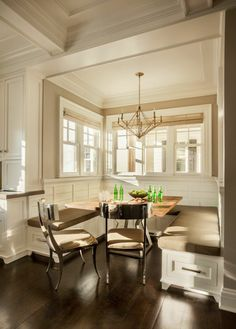 The breakfast nook consists of a U-shaped bench and two chairs with a light wood table in the center. The nook has windows on three sides, which let in the morning light. Above the table is a simple, delicate chandelier.