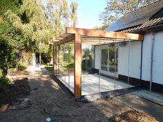 Strak uitgevoerde terrasoverkapping in warm en natuurlijk hout. De perfecte combinatie van materiaal en stijl.
