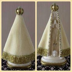 Nossa Senhora Aparecida, em gesso e manto revestido manualmente em pérolas e detalhes em strass, com 30 cm de altura.