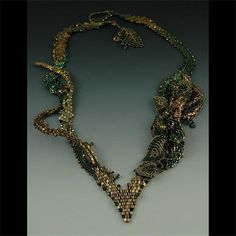 """Gleaming Garden"" : The necklace base is made of diagonal peyote stitch and is embellished with Russian leaves and a gilded flower bud.  A stem of beadwoven branches creeps up one side of the necklace.  The clasp is a double Russian leaf.  By CeeJay Creations"