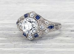 Art Deco ring made in platinum centered by a 1.58 carat GIA certified I color VS2 clarity old European cut diamond. Accented by fancy shaped sapphires and single cut diamonds. Circa 1925. The sapphire