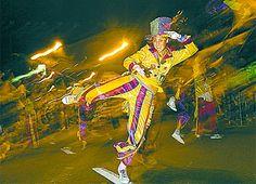 Se observa un acontecimiento artístico: es una murga en un barrio de Buenos Aires. Esta puesta en escena constituye una performance, ya que implica la reiteración de un hecho generado con la finalidad de mantener viva una tradición. Las vestimentas usadas por los bailarines podrían ser consideradas índices -ya que interactuan con los protagonistas en la danza, experiencia material- y símbolos, debido a que una convención social relaciona esta vestimenta con el carnaval como evento cultural.