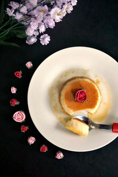 Overhead shot of a white plate of creme caramel topped with a red rose andmore roses around the plate and flowers at the top