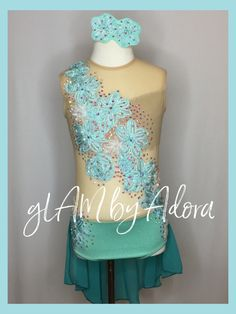 Beautiful mint green/aquamarine leotard with skirt in back,featuring a nude bodice with swirly floral appliqués and loads of Swarovski Crystals in Crystal AB. Definitely sparkle on stage!