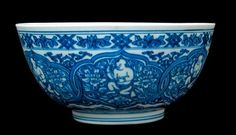 "A Chinese blue and white bowl, Kangxi period , heavily potted of deep ""U"" form, with rounded sides rising from a straight foot, the exterior decorated with six interlocking panels depicting a boy amid lotuses and scrolling foliage, the slightly convex well of the interior with a boy holding a branch of five lotus blossoms amid foliage in a five petalled flower head on a blue ground, the base with an old inventory sticker, 19.9cm wide by 9.1 high"