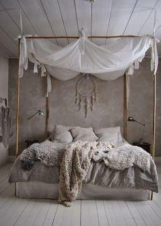 Chambre à coucher avec lit à baldaquin, attrape-rêve suspendu au-dessus du lit, plafond et sol en bois blanchi.