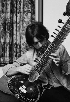 George Harrison playing a sitar at his home, Kinfauns by Henry Grossman - 1967 'George was full of stories about India and his trip. I enjoyed hearing it all. I asked about the sitar and how he was progressing. Sitting cross-legged on a rug and balancing the instrument on his foot, he ran through various exercises he had learned'