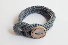 Handgebreide armband in grijs met handgemaakte houten knoop.