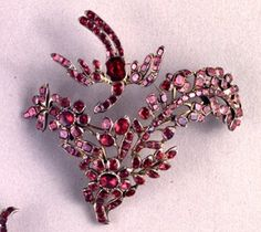 Aigrette; silver-gilt, in the form of a flower spray, with trembler bird; dished closed-back, set with flat-cut garnets.