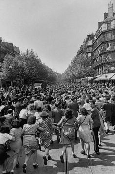 A crowd of jubilant French civilians, running in the streets to celebrate the end of the war in Europe
