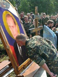 Russian soldiers worshipping an icon of Vladimir Putin before fighting in Ukraine.