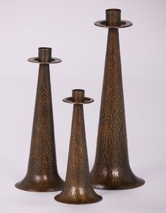 Group of three Arts & Crafts hammered copper candlesticks c1910.  Unsigned.  9.25″h, 12″h & 15″h