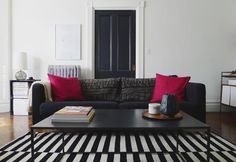Victorian mouldings, black door, vintage radiator, contemporary furniture and monochrome rug