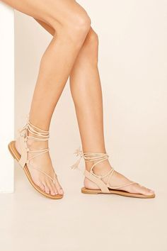 A pair of faux suede sandals featuring a lace-up design and a low heel.
