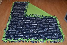 Seattle Seahawks blanket. Fleece fabric tied together. Easy no sew project anyone can do and save a ton of money.  Note to self:  be sure fabric is straight next time!