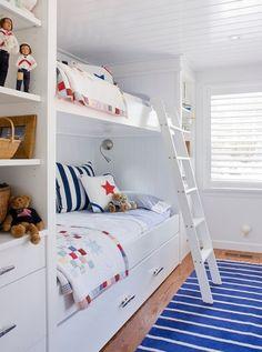 壁のくぼみにベッドがあるという形はすっぽりと何かに包まれて眠る安心感を提供してくれます。2段ベッドですが、それぞれの枕元にはライトがあり、どちらかが眠っていていも邪魔することなく読書などを楽しむことができそうです。ベッドの横は棚になっていて、大好きなおもちゃを飾ったり、洋服をしまったりと空間を有効に使うことができていますね。青を差し色に入れて、海が大好きな子どもたちを楽しい気分にさせてくれます。おもちゃも水兵さんのおもちゃがあり、海を連想させてくれます。全体が板壁でカントリーな印象があり、落ち着いた雰囲気の部屋で自然に触れながら成長することができそうですね。気持ちの良いクッションが部屋にぬくもりをくれています。