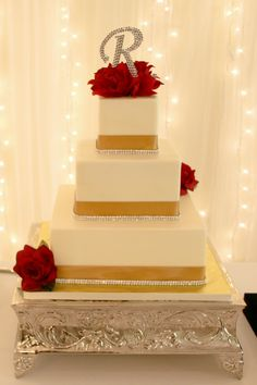 my wedding cake... white butter cream, 3 tiered square vanilla and chocolate marble cake with gold ribbon, rhinestone banding, and red roses
