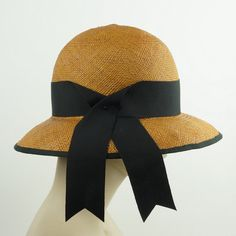 This is a handmade Panama straw hat in a cloche shape with a somewhat wide brim. It is a lovely golden brown color, trimmed in black grosgrain ribbon which is a beautiful color combination.  The cloche has a deep round crown and the brim is The hatband is made of black grosgrain ribbon secured with a tiny vintage button. The brim edge is wired and covered with matching ribbon, all hand sewn using classic millinery techniques, the way womens fine hats were made in the past.  Size 22.25 which…