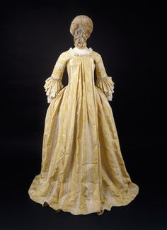 Striped yellow silk sack-back dress (back view), 1770-75. The bodice has robings; all front edges have ruched trimming and the sleeves have falling cuffs.