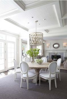 Chic dining room features a coffered ceiling accented with beadboard panels lined with a silver drum pendant, Worlds Away Leona Silver Leaf Pendant, hanging over a round salvaged wood dining table surrounded by white round back French dining chairs atop a charcoal gray rug.