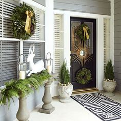 Create an elegant wintertime entryway with a gold starburst mirror set between two wreaths. Fir trimmings and apainted papier-mache deer (protected from the elements by the porch) spruce up a cement ledge while gold ornaments accent the topiaries./