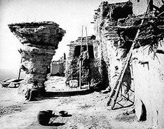 Dancers' Rock, Walpi, Arizona, part of a Hopi pueblo; picturing three Hopi people, ladders, and utensils.  Photographed by John K. Hillers, 1879.