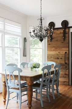 Pair painted, formal chairs with wooden, farm table. Oversized, rustic wooden doors and chandelier complete the study in contrasts.