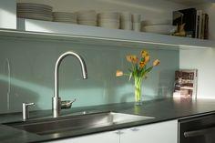 Кухонный фартук за кухонной раковиной выполнен из матового стекла и именно он формирует интересный полупрозрачный проем в гостиной. .