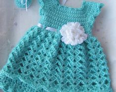 This listing is for a baby dress, maryjane and headband set. This dress is made out of a soft sparkly brown yarn with a cream colored bottom. The ribbon ties in the back and is an antique gold color. There is a little pink flower attached to the dress. The headband and shoes are made to match the dress. This set come in 3 different sizes.  Newborn Size: Headband up to 13 inches, shoes 3 inches 0-3 Months: Headband up to 14 inches, shoes 3 1/4 inches 3-6 Months: Headband up to 14-16 inches…