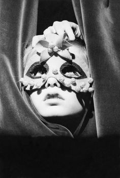 A young Twiggy wearing a mask and peeking through the curtains of the Paris shop Torrente, 1967