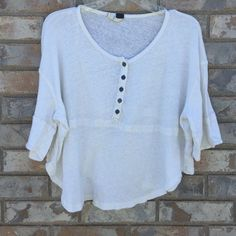 We the Free People Top Off white color. Worn 3x. Longer in the front and shorter on the sides so kind of cropped. Super comfy and cute over dresses, long sleeve shirts, high waisted pants, as a light yoga top etc. Great for layering. Free People Tops