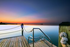 Nadia Sanowar Photo. Early morning,sunrise over the coastline in Antalya Turkey. From the long wooden pier, I used long exposure to smooth the water in the bay. Caught the sun rising just above the other jetty in the distance over the ocean