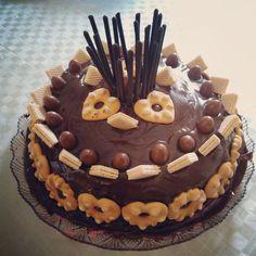 Come si prepara la torta di compleanno al cioccolato e biscotti per bambini, un pan di spagna ricoperto di glassa di cioccolato e decorata con biscotti