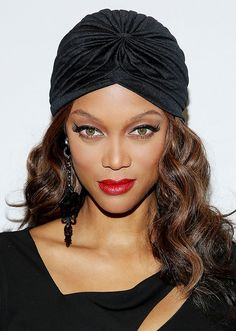 Tyra Banks rocks a cool turban with her glam cat eye makeup and bright red lips