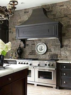 stone wall, stainless appliance, grey hood