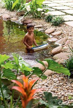 No tanque com margem de seixos, Lucas brinca entre carpas de verdade – cabe aos papiros, plantados em vasos submersos, a tarefa de manter a água limpa.