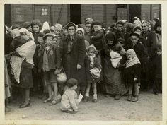 """Women and children on the Birkenau arrival platform known as the """"ramp"""". The Jews were removed from the deportation trains onto the ramp where they faced a selection process - some were sent immediately to their deaths, while others were sent to slave labor"""