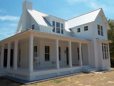 Love this white farmhouse with standing seam room.