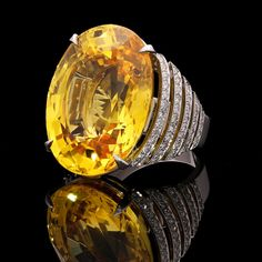 An exceptional 63.80ct unheated yellow sapphire and diamond ring